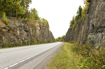 Highway among granite rocks in early autumn.
