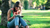 Young pretty woman reading book by the tree in park