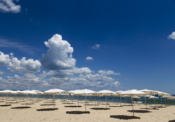Panoramic view of straw umbrella on an empty beach