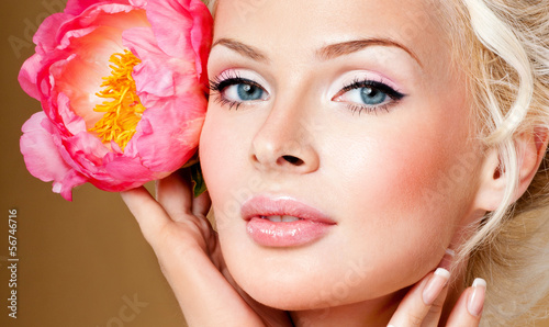 beautiful blonde   girl with pink flower. perfect skin.