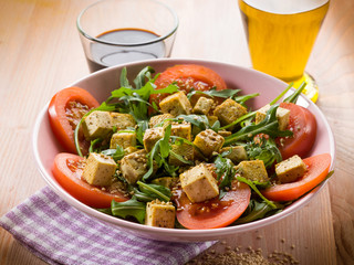 salad with tofu tomatoes arugula and sesame seeds