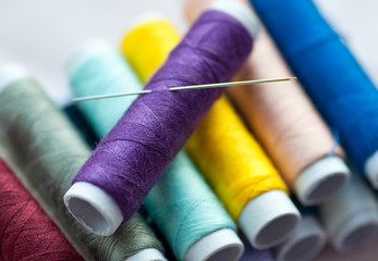 New spools of colourful thread with sewing needle