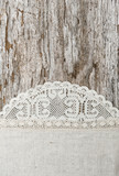 Linen fabric with lace on the old wooden background
