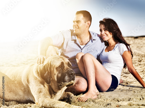couple with pet dog on the beach