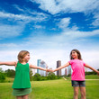 Two sister girls friends playing holding hand in urban skyline