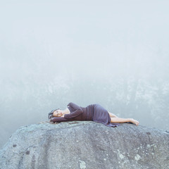 young girl lies on a big stone