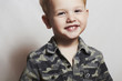 smiling child. funny little boy. 4 eyers old. military shirt