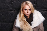 Beautiful blond woman in a fur near bricks wall. winter