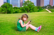 Blond kid girl playing with smartphone sitting on park lawn at c