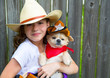 Beautiful cowboy kid girl holding chihuahua with sheriff hat