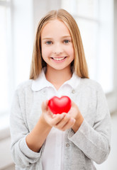 beautiful teenage girl showing red heart