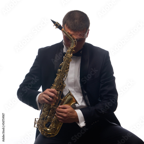 Isolated portrait of sitting saxophonist in tuxedo