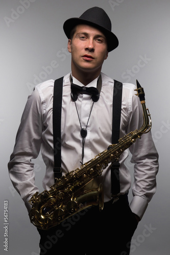 Portrait of saxophone player with hat. DJ with sax