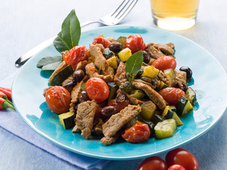 meat stew with tomatoes zucchinis and olives