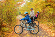 Happy family on bikes in autumn park, having fun - 56756923