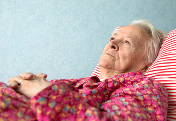 Old  sick woman lying at bed