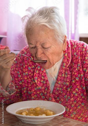 Senior woman eating soup