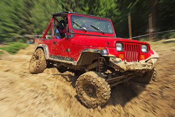 Red off-road car in difficult terrain