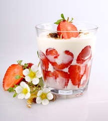 Strawberry with yogurt in glass, flowers and cereal