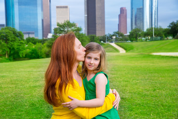Mother and daughter happy hug kiss in park at city skyline