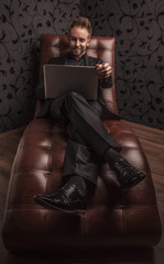 Handsome young man in dark suit relaxing on luxury sofa.