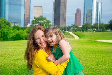 Mother and daughter happy hug laughing in park at city skyline