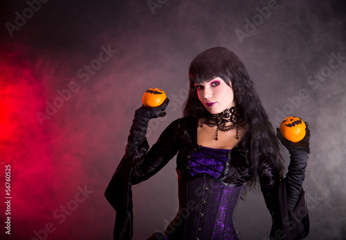 Portrait of attractive witch in purple gothic Halloween costume