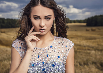 Young woman in fashionable dress pose outdoor on sky background.