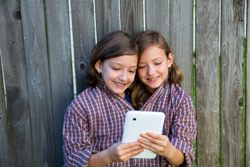 twin girls dressed up pretending be siamese and tablet pc