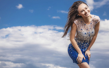 woman in a fashionable dress pose outdoor on sky background.