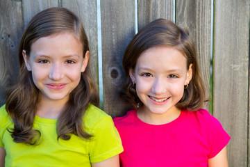 Happy twin sisters smiling on wood backyard fence