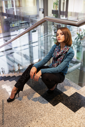 Young business woman sitting on the steps in office interior