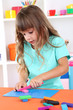 Little girl molds from plasticine sitting at table in room