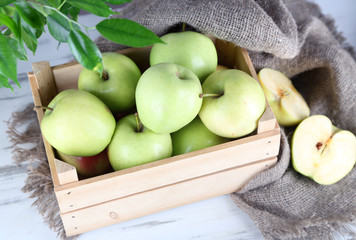 Juicy apples in box on wooden table
