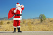 Santa claus holding a bag full of gifts on a road and looking