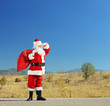 Santa claus with bag full of presents standing on an open road a