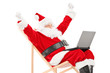 Santa Claus sitting on a chair with laptop gesturing happiness