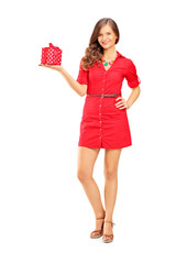 Attractive smiling woman in dress with a gift looking at camera