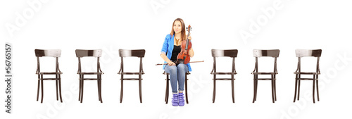 Casual woman seated on a chair holding a violin and waiting