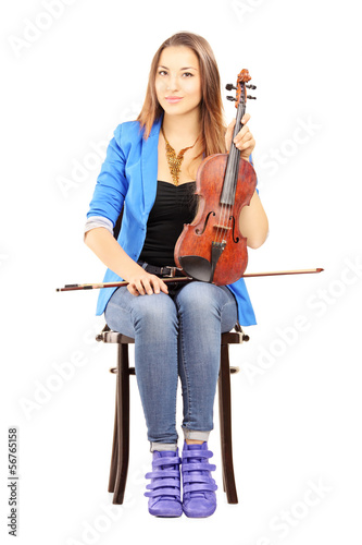 Casual young woman seated on a wooden chair holding a violin
