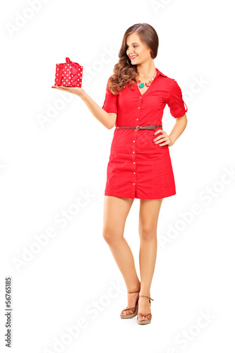Attractive smiling woman in red dress holding a gift