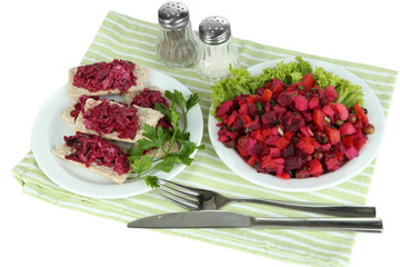 Beet salad on toasts and on plate isolated on white