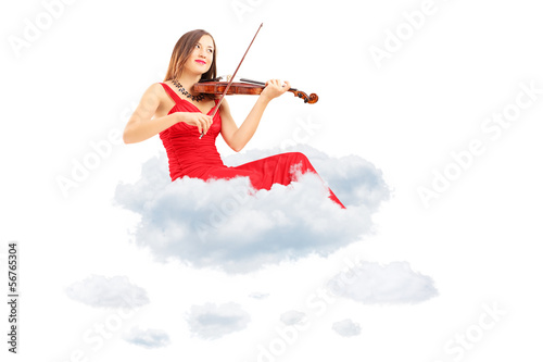 Young woman in red dress playing the violin seated on clouds