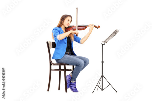 Young woman on a wooden chair playing the violin