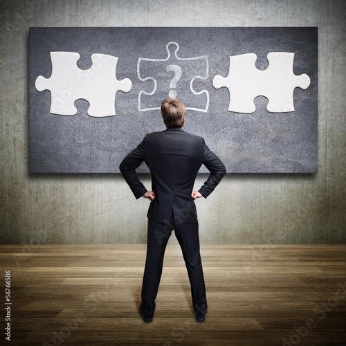 Geschäftsmann vor fehlendem Puzzlestück