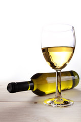 White wine glass and recumbent bottle on wooden table