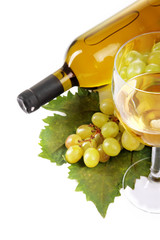 White wine glass, grapes and wine bottle on vine leaf