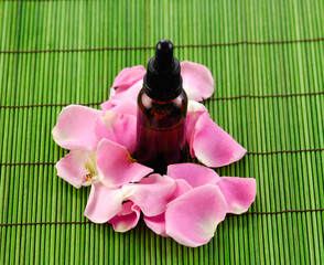 rose petals and massage oil on green mat