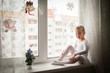 Girl sitting on a windowsill, on the window snowflakes