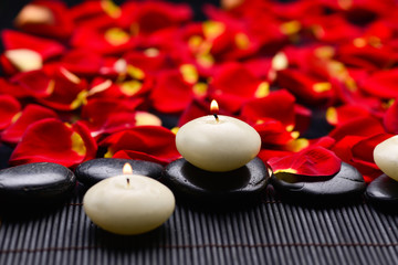 Stones with candle on mat with red rose petals